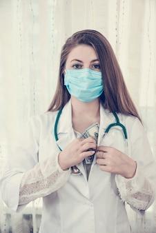 Dottore che nasconde una tangente in dollari nella veste, corruzione in medicina