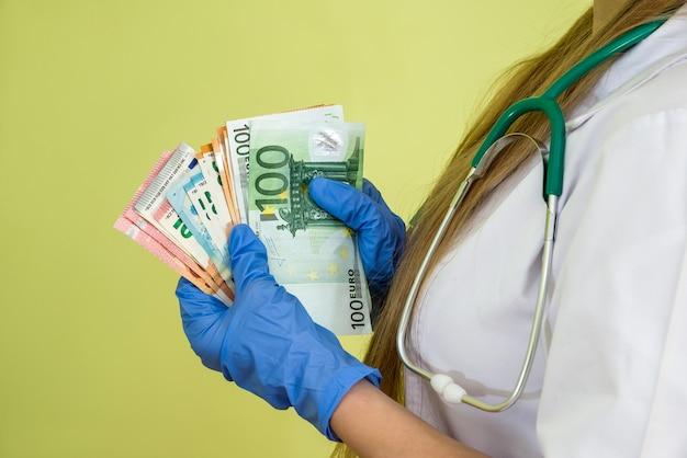 Soldi dell'euro della tenuta del medico isolati sul verde