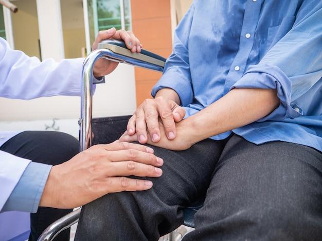 Aggiusti il paziente della mano della tenuta sulla sedia a rotelle.