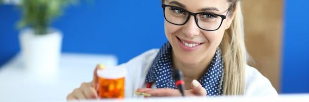 Medico tenere un barattolo di pillole nelle mani e indicare la fotocamera del computer portatile.