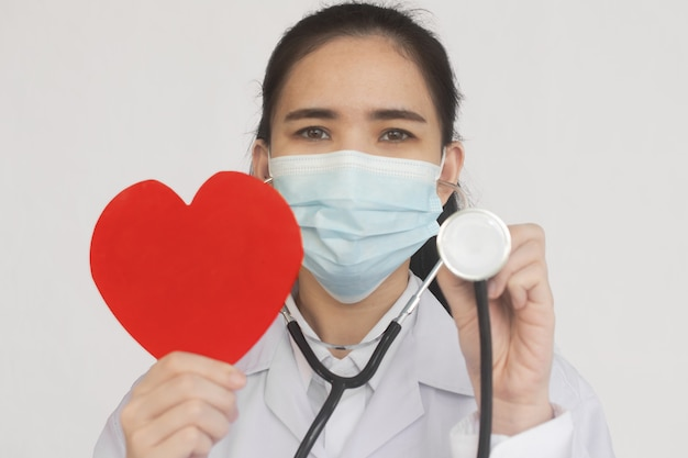 Stetoscopio della stretta del medico controlla il cuore rosso