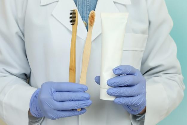 Medico tenere dentifricio e spazzolini da denti su sfondo blu
