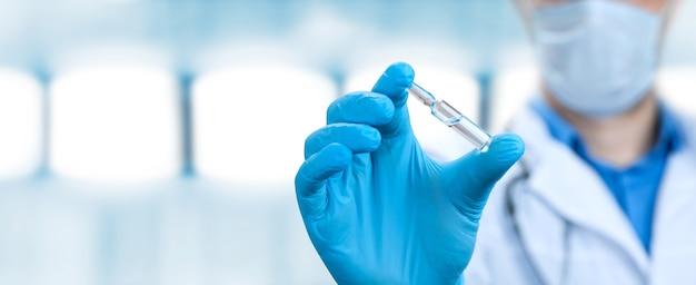 Il medico tiene una viola con il vaccino contro il virus corona.