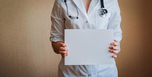 Medico che tiene bandiera bianca in bianco