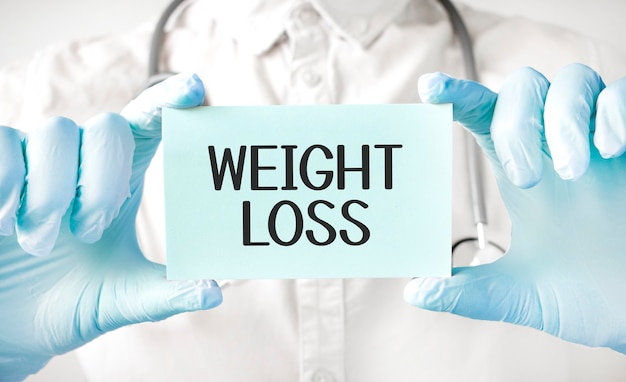Medico tenendo la carta in mano e indicando la parola perdita di peso