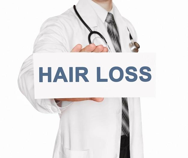 Medico che tiene una carta con perdita di capelli, concetto medico