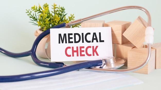 Medico in possesso di una carta con controllo medico, concetto medico. blocchi di legno, stetoscopio, fiori