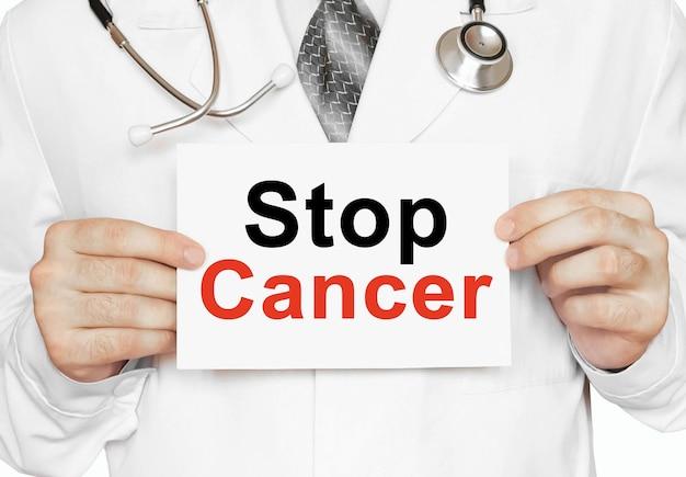 Medico che tiene una carta con stop cancer, concetto medico
