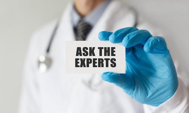 Medico che tiene una carta con testo chiedi agli esperti, concetto medico