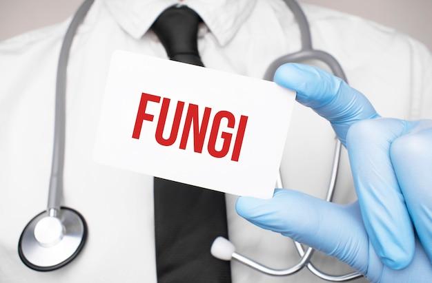 Medico che tiene una carta con testo funghi, concetto medico