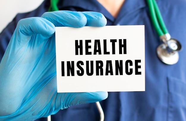 Medico in possesso di una carta con testo assicurazione sanitaria.