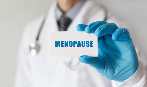 Medico in possesso di una scheda con testo menopausa, concetto medico