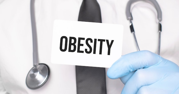 Dottore in possesso di un biglietto con testo obesità