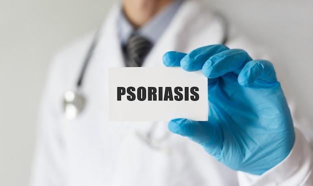 Medico in possesso di una scheda con testo psoriasi, concetto medico