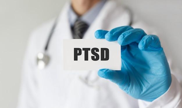 Medico in possesso di una carta con testo ptsd, concetto medico