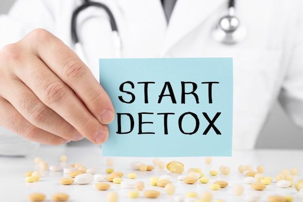 Medico che tiene una carta con testo start detox, concetto medico