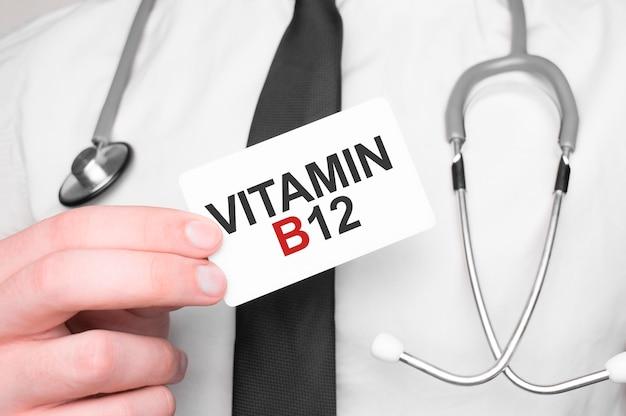 Dottore in possesso di un biglietto con testo vitamin b12 Foto Premium