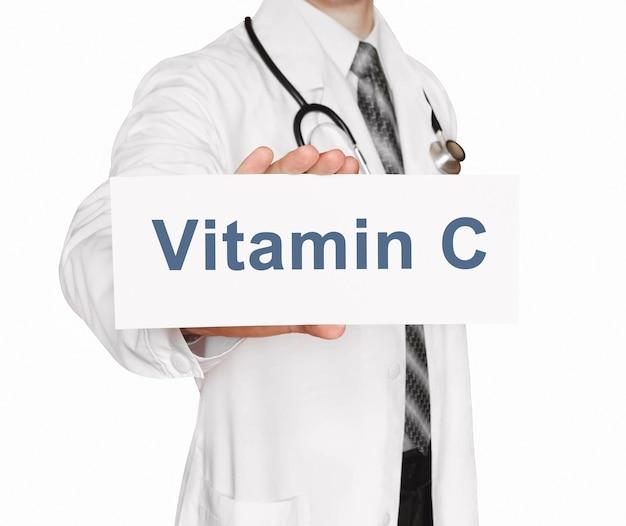 Medico che tiene una carta con vitamina c, concetto medico