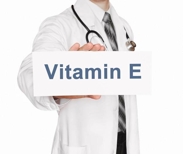 Medico in possesso di una scheda con vitamina e, concetto medico