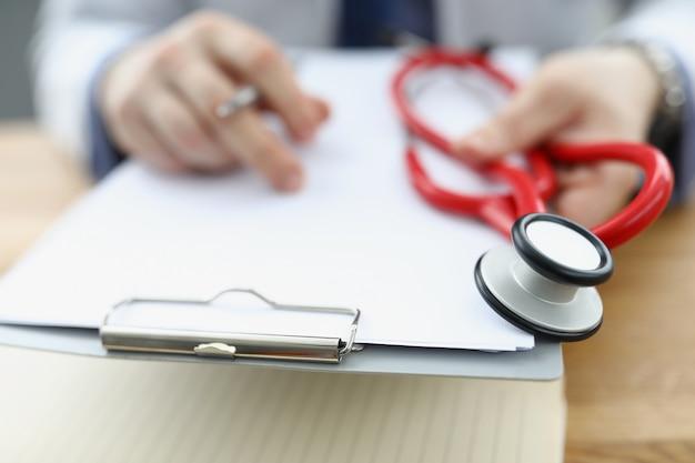 Medico che tiene appunti con documenti e stetoscopio rosso in primo piano delle mani