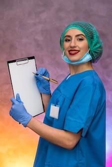 Lavagna per appunti della tenuta del medico con la penna. bella donna in forma medica sorridente