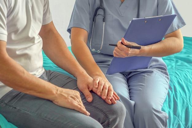 Medico che tiene la mano dell'uomo anziano e lo conforta