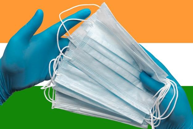 Medico che tiene le maschere per il viso nelle mani guanti blu medici sullo sfondo bandiera nazionale dell'india concept