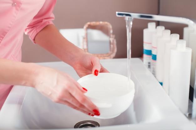 Medico che tiene in una mano una ciotola cosmetica di riempimento di acqua dal rubinetto.