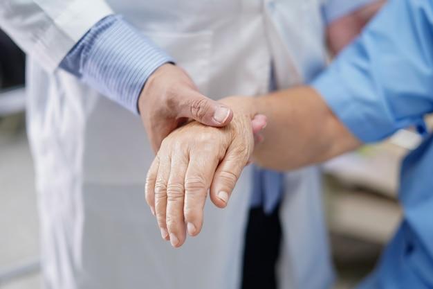 Medico che si tiene per mano paziente senior asiatico della donna con amore.