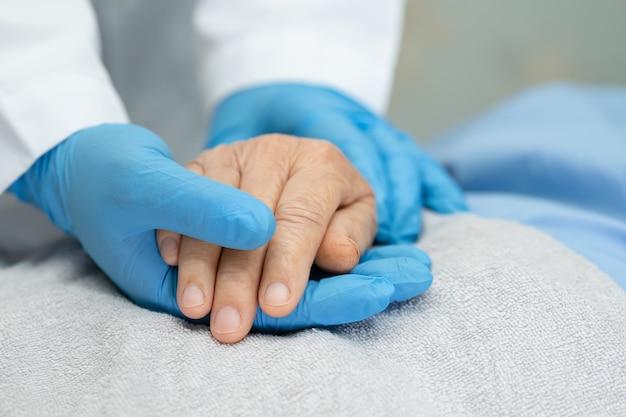 Medico che tiene le mani paziente anziano asiatico della donna con amore.