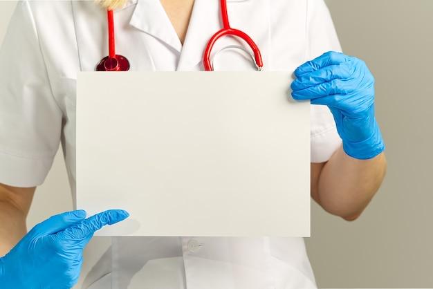 Medico che tiene in mano la bandiera bianca in bianco, mockup