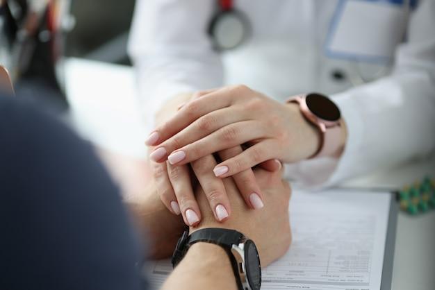 Medico che tiene le mani del paziente in primo piano dell'ufficio. concetto di diagnosi fatale