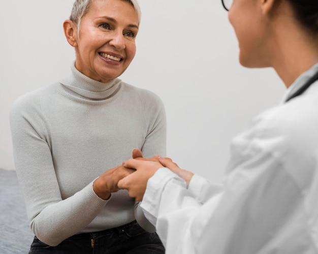 Medico che tiene le mani con paziente felice