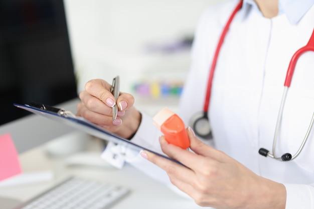 Medico che tiene inalatore nelle sue mani e scrive il primo piano di storia medica. prescrizione ormonale