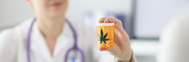 Medico che tiene un barattolo di pillole di marijuana closeup marijuana