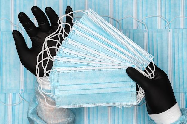 Medico che tiene in mano molte maschere mediche chirurgiche blu in guanto protettivo nero nelle mani. immagine concettuale sullo sfondo di bendaggi respiratori di gruppo per viso umano con cinturini per le orecchie in gomma.