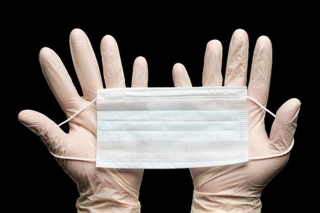 Medico che tiene la maschera medica in due mani in guanti bianchi isolati su sfondo nero