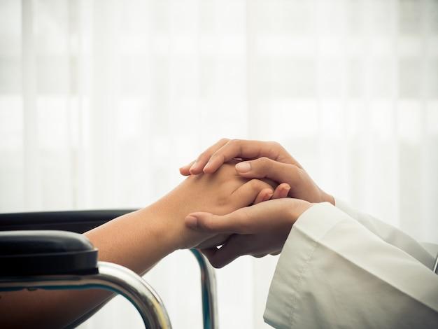 Aggiusti la tenuta della mano del paziente insieme su fondo bianco vago.