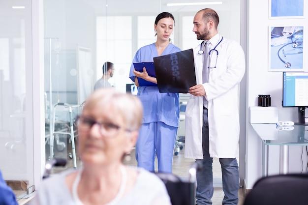 Medico che tiene i raggi x del paziente che spiegano la diagnosi all'infermiera nell'area di attesa