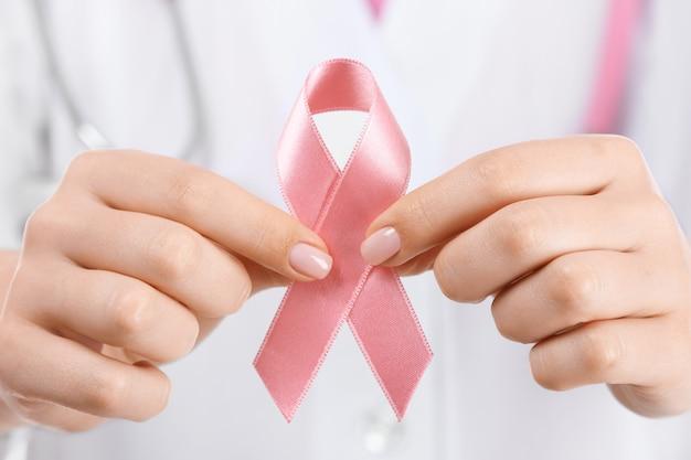 Medico che tiene nastro rosa, primo piano. concetto di consapevolezza del cancro al seno