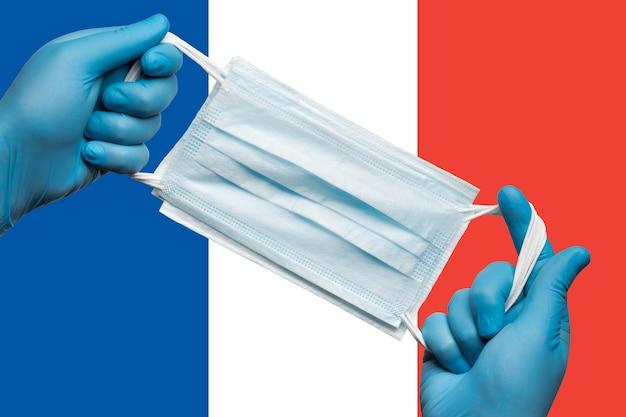 Medico che tiene in mano una maschera respiratoria in guanti blu su sfondo bandiera bandiera della francia o tricolore francese. concetto di quarantena del coronavirus e epidemia di pandemia. benda medica per viso umano