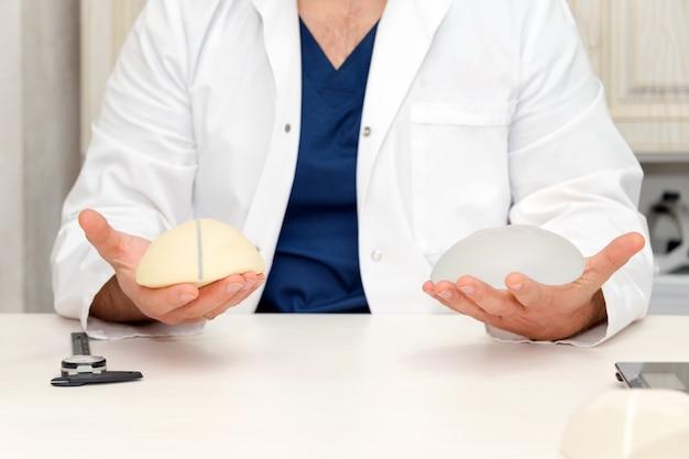 Medico che tiene protesi al silicone per l'aumento del seno, spazio per il testo. mani del chirurgo plastico che tengono protesi mammarie al silicone. chirurgia plastica