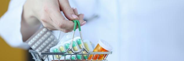 Medico che tiene un piccolo cesto della spesa con il concetto di business farmaceutico del primo piano dei farmaci