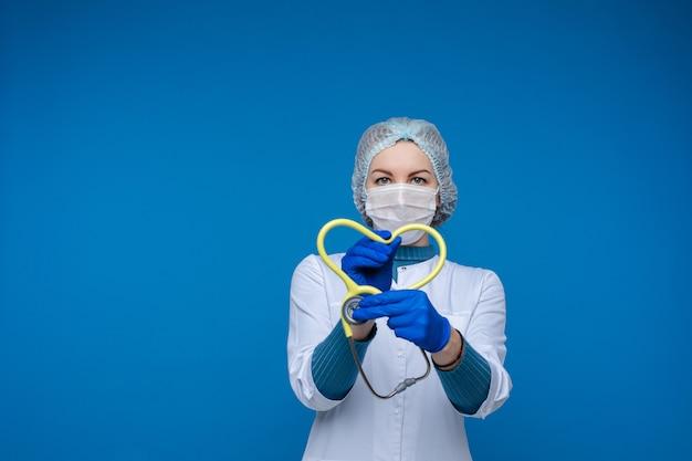 Stetoscopio della holding del medico a forma di cuore. lotta contro il concetto di pandemia.