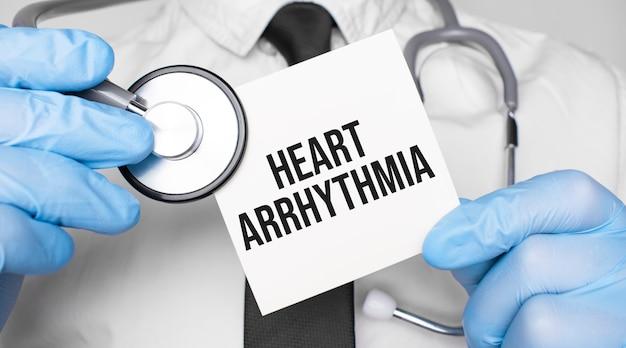 Medico che tiene stetoscopio e foglio di carta con testo aritmia cardiaca. concetto medico