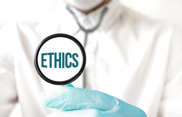 Medico che tiene uno stetoscopio con testo etica, concetto medico