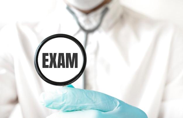 Medico in possesso di uno stetoscopio con testo esame, concetto medico