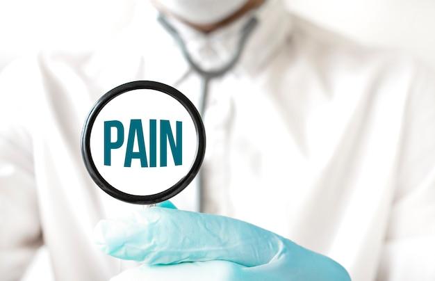 Medico che tiene uno stetoscopio con testo dolore, concetto medico