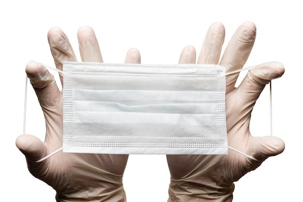 Medico che tiene la maschera per il viso medica chirurgica nelle mani in guanti isolati su sfondo bianco