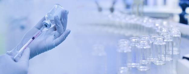 Medico che tiene la fiala del vaccino della siringaconcetto di ricerca farmaceutica della medicina